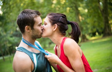 Young happy fitness couple kissing - woman put skipping rope around men's neck