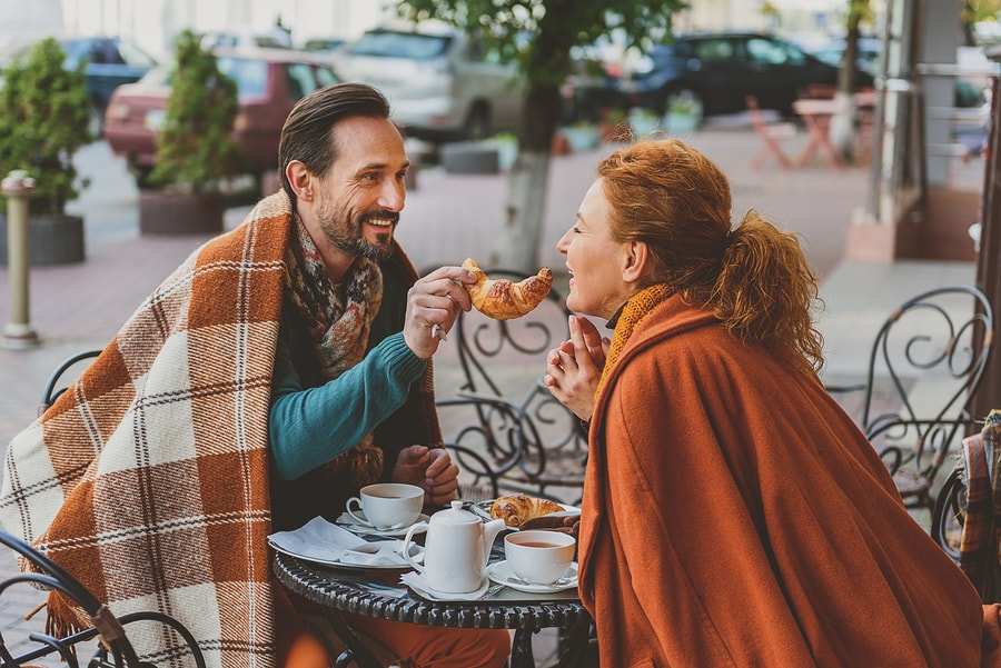 Happy lovers are enjoying breakfast in cafe outside. Man is feeding woman with croissant and smiling. He is covered by warm blanket