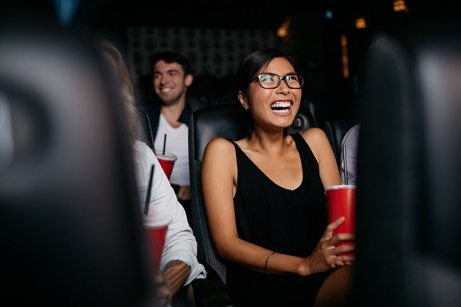 Shot of young woman sitting in multiplex movie theater watching movie and laughing.