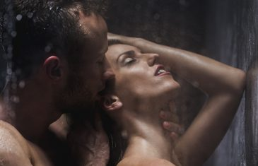 Handsome man kissing and embracing his sexy girlfriend under shower