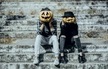 Halloween hipster couple with pumpkin heads. Man and woman sitting on grey stairs. Girl in black felt hat. Halloween jack o lantern symbols. Holiday celebration concept.