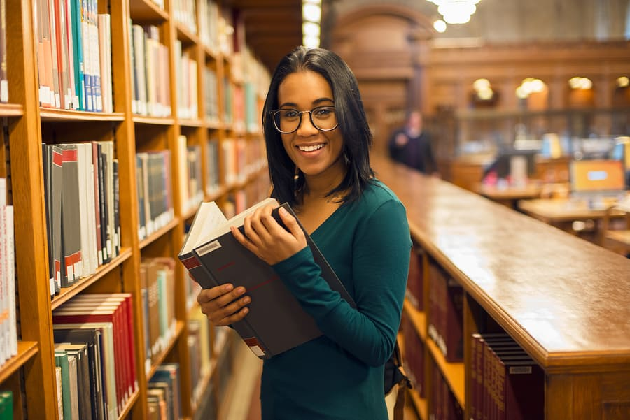 girl reading book at library