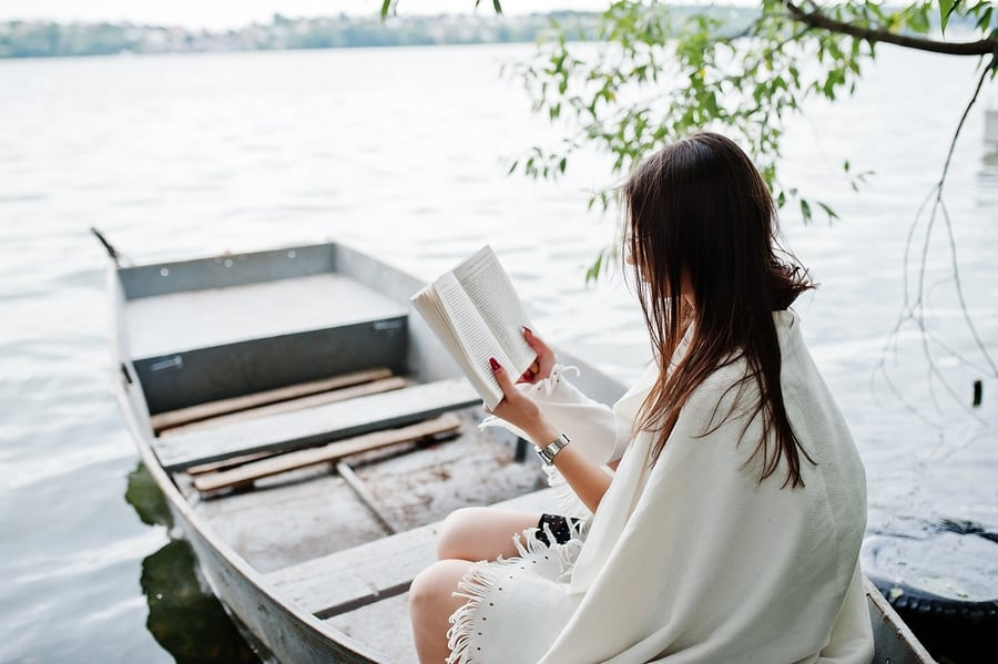 woman reading a book in a boat